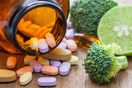 medicine bottle with tablets inside next to broccoli to represent weightloss pills
