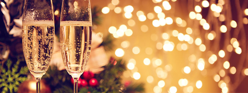 two glasses of champagne in front of christmas lights