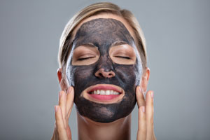woman with activated charcoal face mask to show benefits to skin