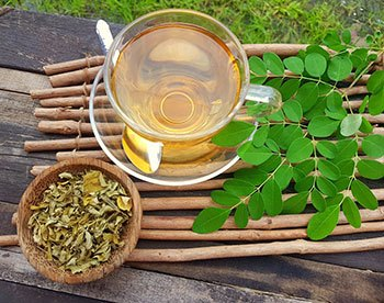 pot of dried moringa leaves next to a cup of green tea