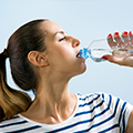 woman drinking water from a bottle to show that she is not dehydrated