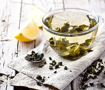 a glass filled with green tea leaves and hot water next to diced lemons