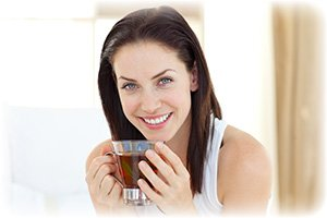 Woman Drinking Green Tea while smiling to the camera