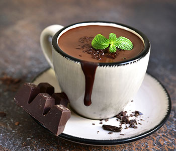 mug filled with hot chocolate with dark chocolate next to it