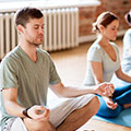 Man and Woman sitting on two yoga mats meditating together