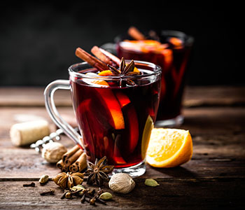 Two glasses of mulled wine on a wooden table with cinnamon