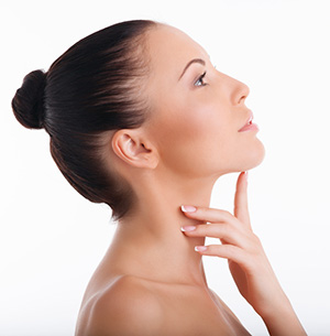 Woman looking up and pointing to chin to show no double chin