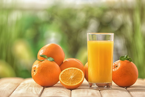 photograph of oranges next to a glass of orange juice