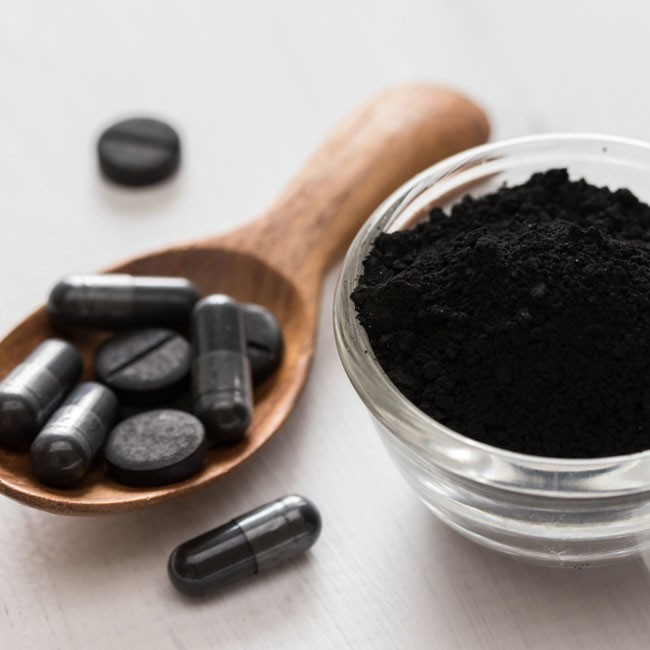 image of a spoon of activated charcoal powder with a cup of capsules next to it