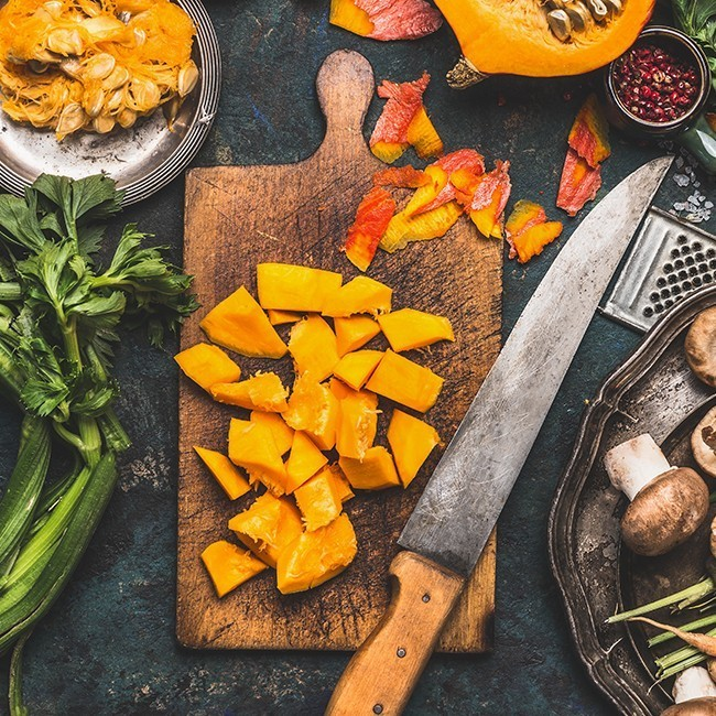 Diced pumpkin on a chopping board with a knife next to various vegetables