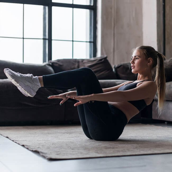 woman doing an exercise position in a living room to show exercises you can do at home