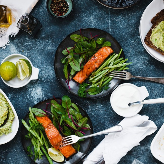 Two plates of grilled salmon with greens next to a tub of yogurt and bowl of slided lime