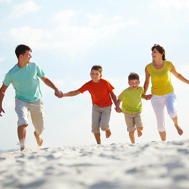 family consisting of mum dad and two young boys running on a beach to represent healthy happy lifestyle