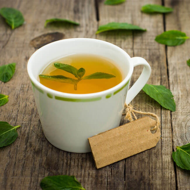 image of a cup of green tea surrounded by green tea leaves