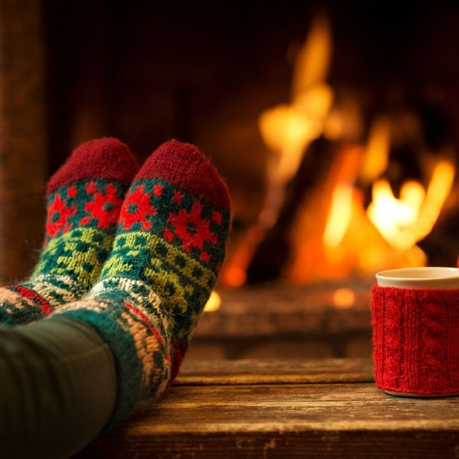 woman wearing christmas socks next to the fireplace with a cup of tea