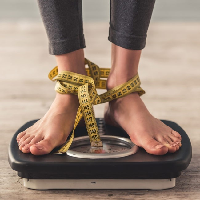 woman standing on weighing scales that has a tape measure tied to her feet