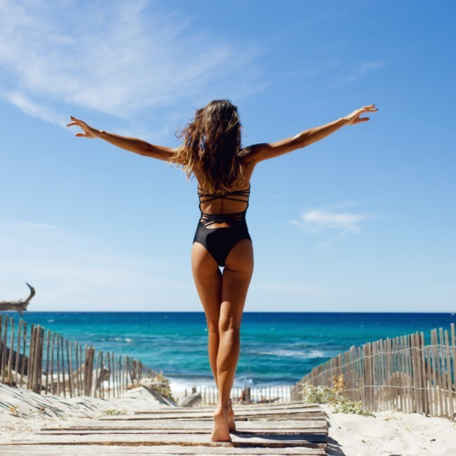 Woman walking towards a beach spreading her arms in the air