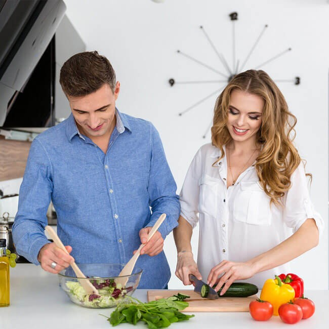 man and woman preparing a salad to show how to balance metabolism