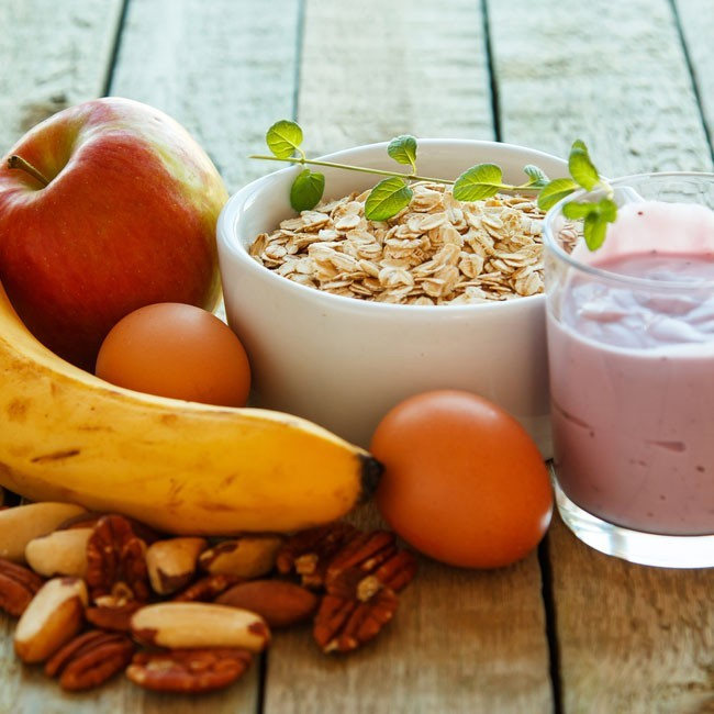 bowl of oats with a glass of yogurt, fruits and nuts