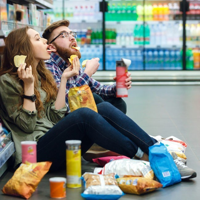 Man and woman sitting on supermarket floor eating crisps with crisp containers and bags on the floor