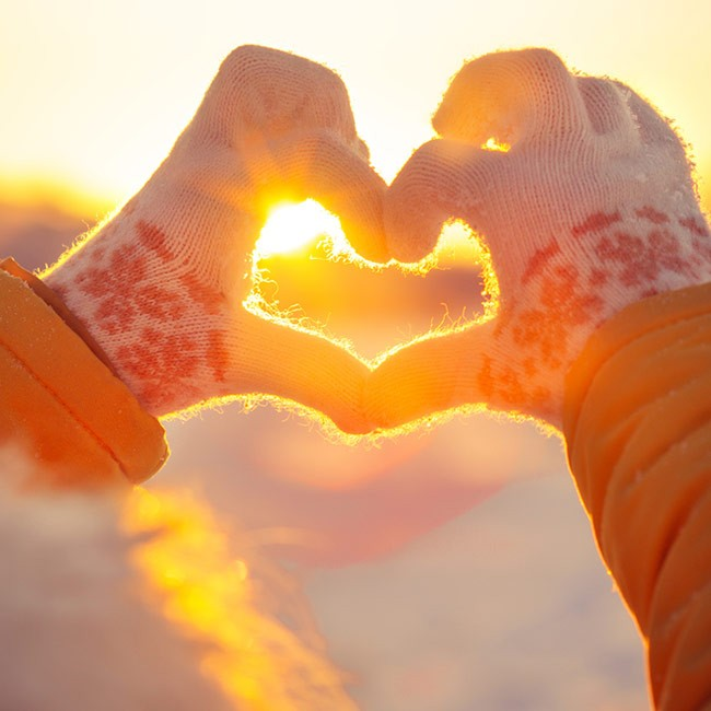 womans hands with gloves showing heart with fingers in cold weather