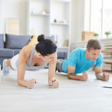 man and woman doing a plank in a living room to show exercises you can do at home