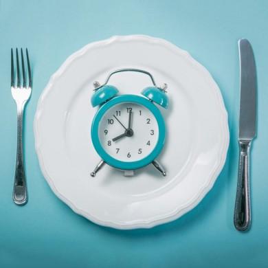 A dinner plate with knife and fork either side with a blue alarm clock in the middle of the plate