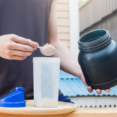 man putting protein powder fro a black tub using a spoon into protein shaker