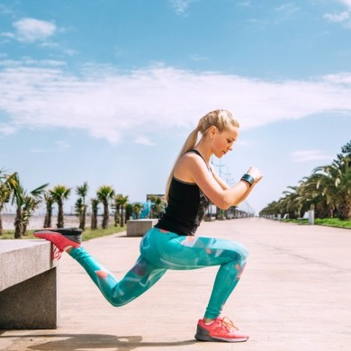 woman dressed in running clothes stretching to show her getting ready for summer