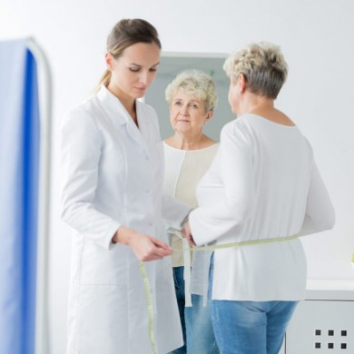 image of a doctor measuring a womans waist to show menopause and weight loss