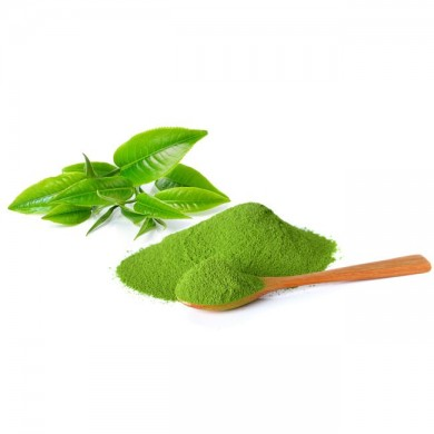 a pile of moringa powder with a spoonfull of moringa powder next to some moringa leaves