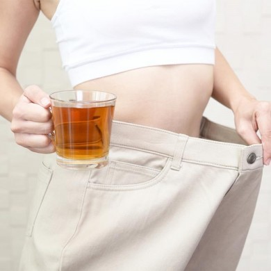 woman with oversized trousers showing space between trouser and waist holding a cup of slimming tea
