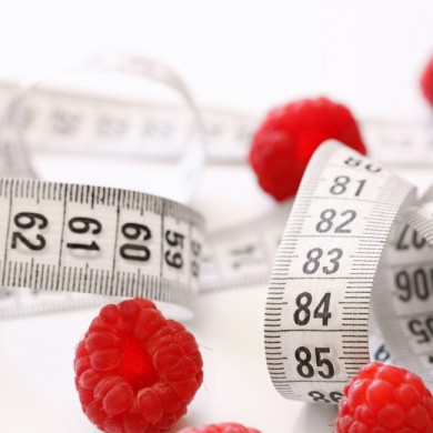 a couple of raspberries laying next to a measuring tape