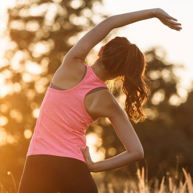 woman in gym clothes doing stretches to indicate she is stretching after a workout