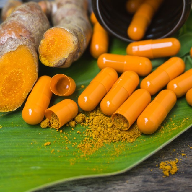 image of turmeric capsules with turmeric powder and ginger