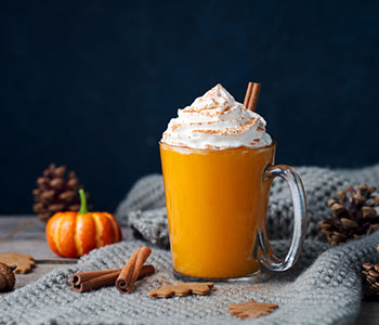 mug filled with pumpkin spiced latte and topped with whipped cream next to a small pumpkin