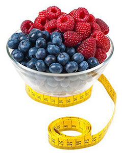 Bowl of raspberries and blueberries with a tape measure around it