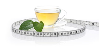 cup of green tea with a leave next to it surrounded by a tape measure