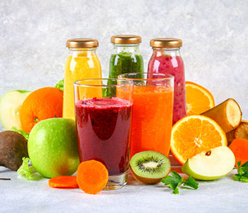 Two different coloured smoothies in glasses in front of three bottled smoothies in front of different coloured fruits