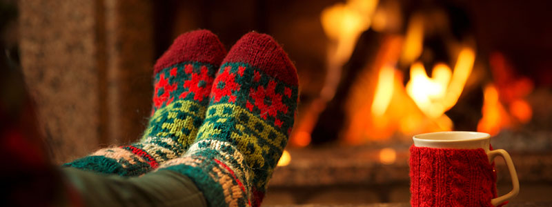 woman with christmas socks next to fire with a cup of tea