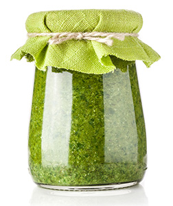 glass jar of spirulina extract in it covered with cloth and elastic band