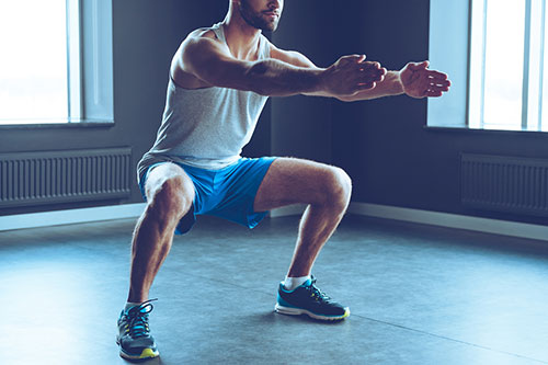 man doing a squat position to show exercise number two