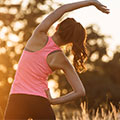 woman dressed in running clothes stretching to show it aids recovery