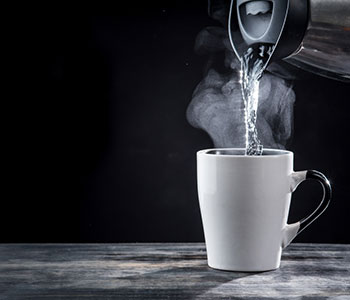 a mug being filled with hot water from a boiling kettle