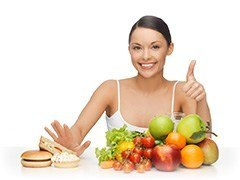 woman saying no to burgers and unhealthy foods and putting thumbs up to fruit and vegetables