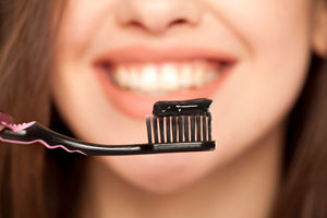 woman with toothbrush with activated charcoal toothpaste