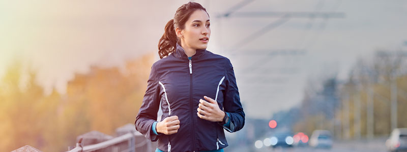 image of woman running on the side of the road to show get moving paragraph