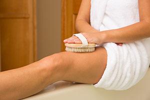 Woman Scrubbing Legs WIth A Body Brush