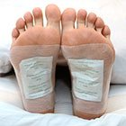 photograph of feet wearing two detox foodpads on foot